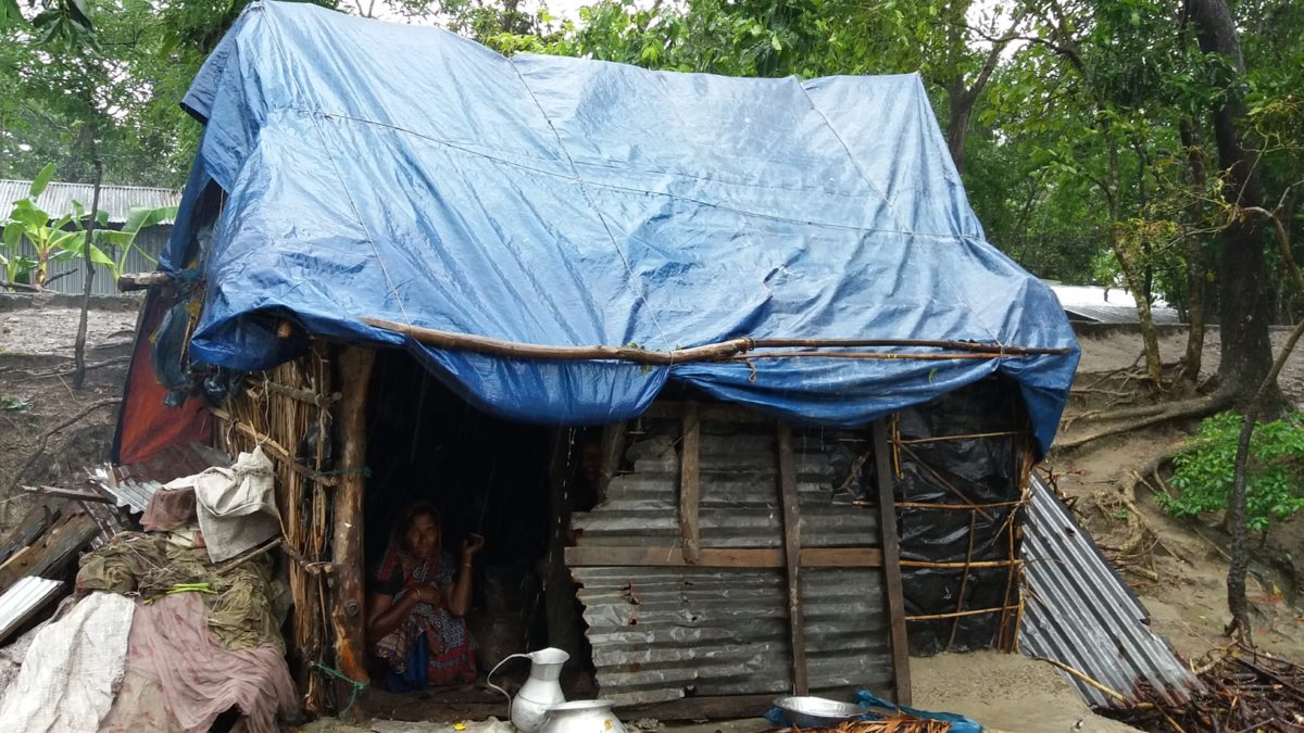 Woman sitting in repaired house in natural disaster affected Bangladesh