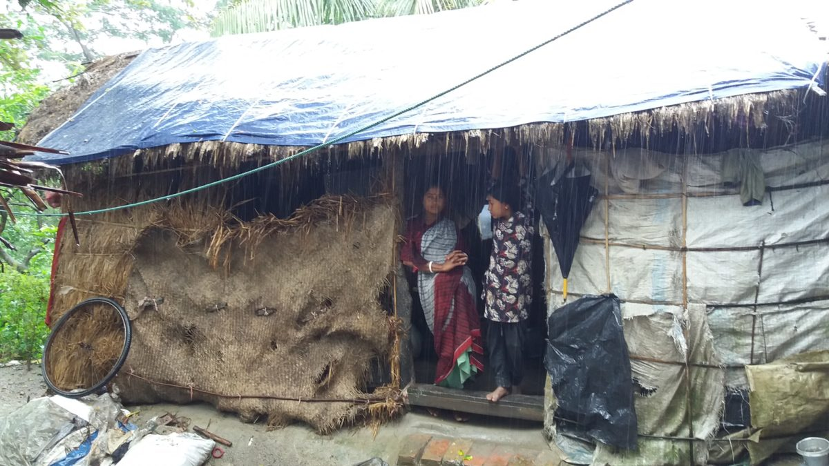 Woman in Bangladesh staying at their house while it is strongly raining