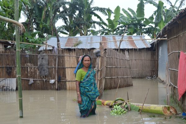 Woman standing in flooded house in bangladesh