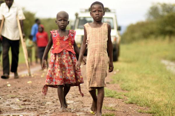Girls walk along a flooded street