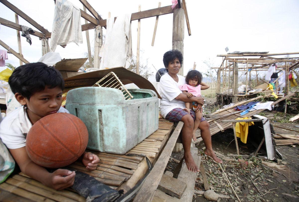 Family sitting on damaged house