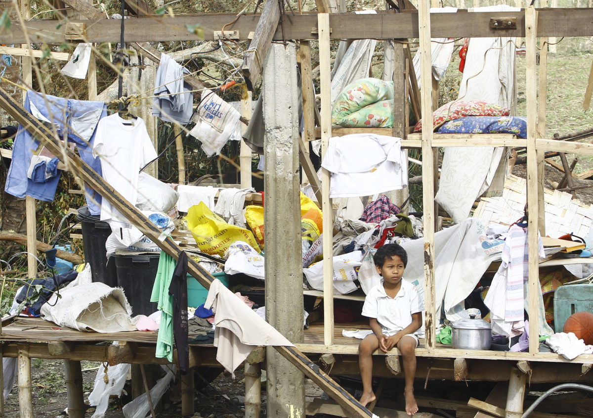 Boy sitting on destroyed house