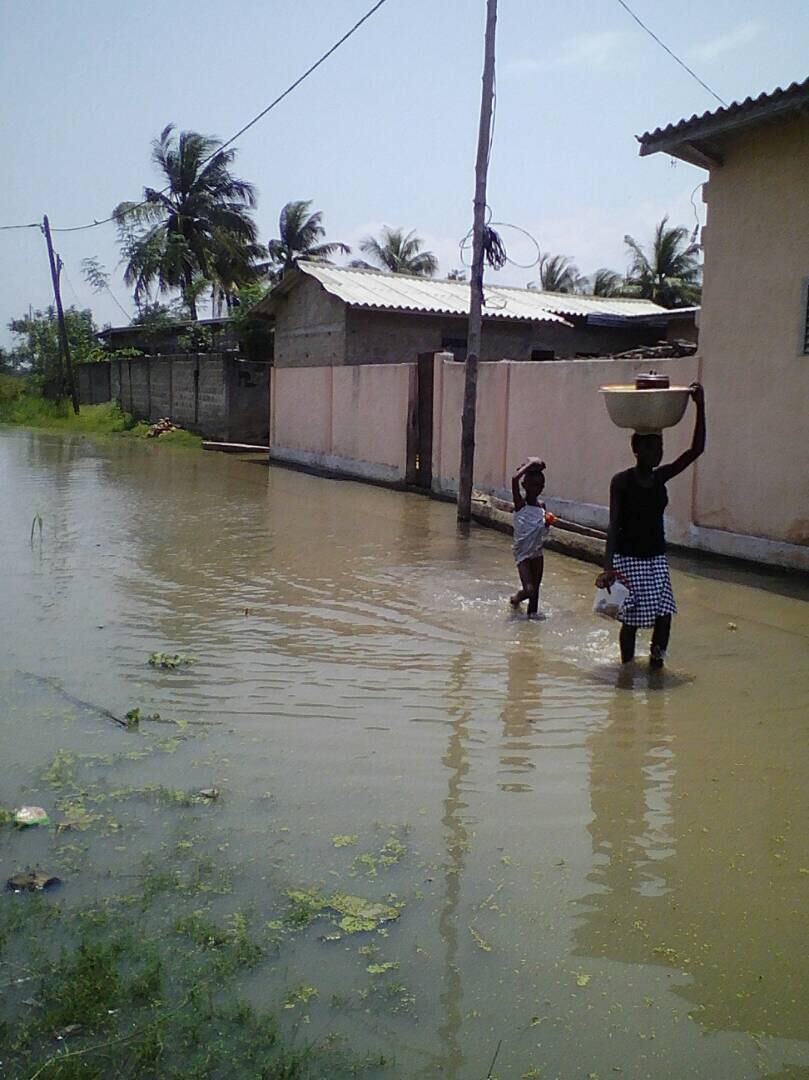 People walking along a flooded street